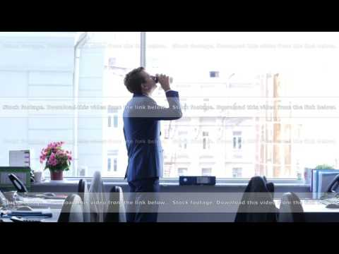 A businessman with coffee thinking and looks out the window in a contemplative way, 4k UHD 2160p