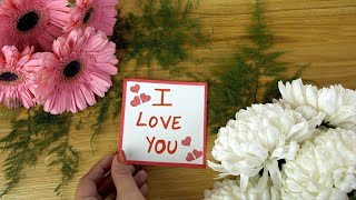Woman hands placing 'I Love You' message card on a decorated wooden surface