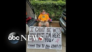 Man holds sign outside hospital as wife receives chemotherapy   WNT