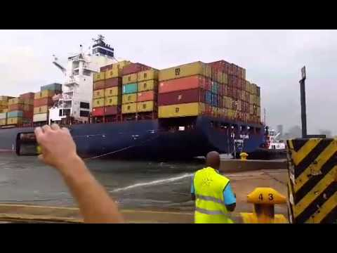 Wind blows container ship against wharf