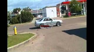 a manual nissan right hand drive car starting up and driving off from the 34st 7eleven edmonton