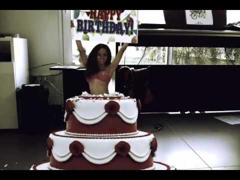 une femme qui sort d'un gâteau d'anniversaire est qui dit joyeux