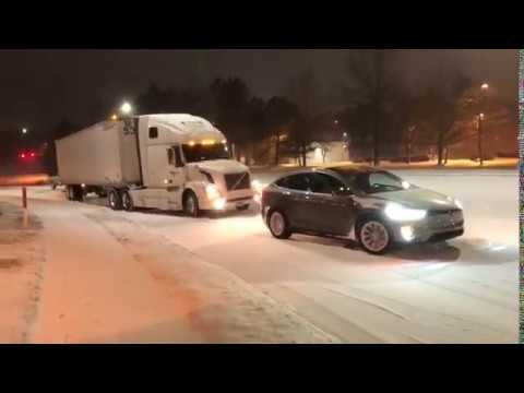 Electric Tesla Model X Towing a Semi Truck Stuck in the Snow