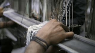 Closeup shot of worker pulling threads through the heddles