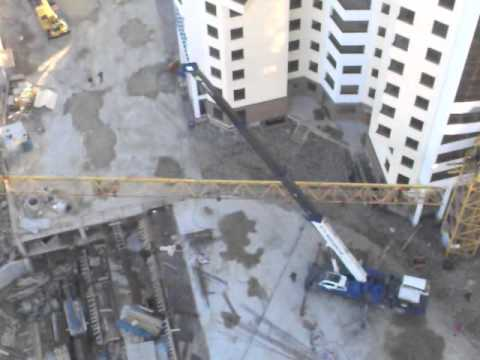Автомобильный кран снимает стрелу башенного крана