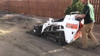 Leveling topsoil with land plane, mini skid