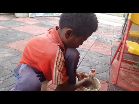 An african boy giving me the cheapest service in cleaning my dirty shoes.