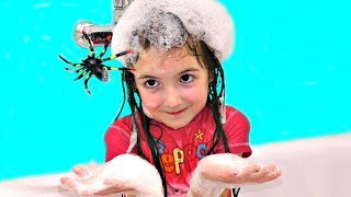 Little girl plays with toy spider in the bathroom