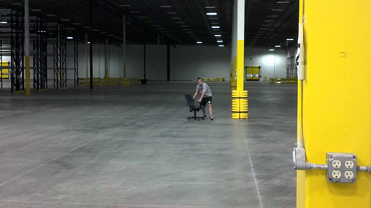 Logan acting silly by riding an office chair in a warehouse - YouTube
