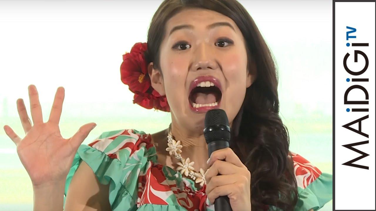 ハワイアンな恰好をしてマイクを持つ芸人、横澤夏子