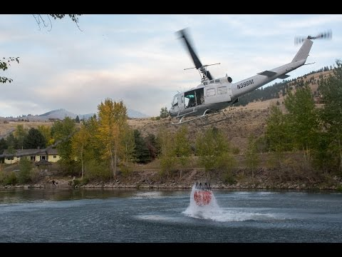 Wildfire fighting helicopters filling drop buckets
