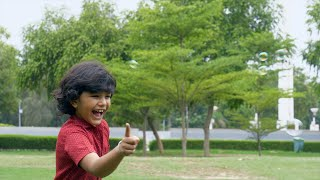 Excited Indian boy playing with soap bubbles in a park - happily enjoying his leisure time