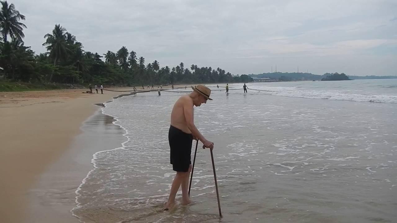 Sri Lanka, Retired Grandpa walks beach Indian Ocean