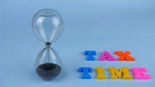 "Closeup shot of a sand clock and ""Tax Time"" words composed with plastic letters"