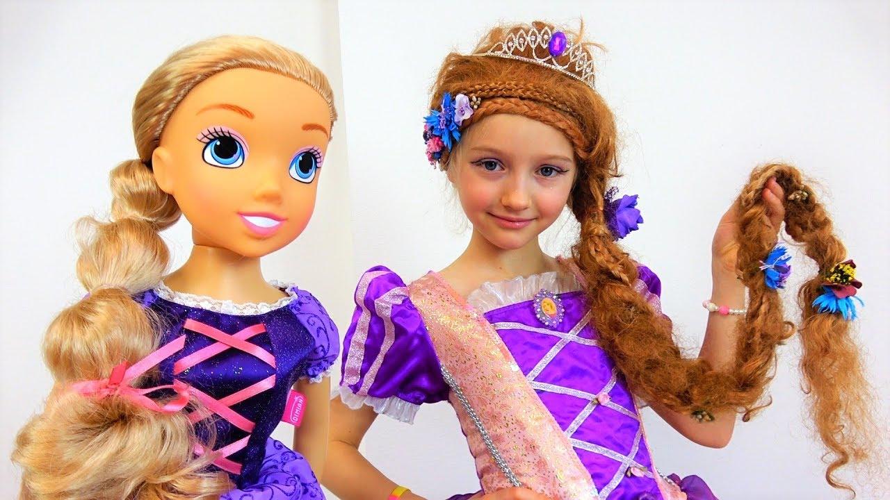 Полина играет с куклой в красивом платье принцессы Рапунцель