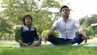 Handsome man and his kid doing yoga exercises while sitting on a yoga mat in a park