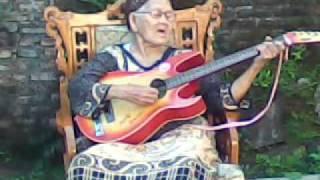 Nenek Gaul Main Gitar Klasik di Beranda Rumah