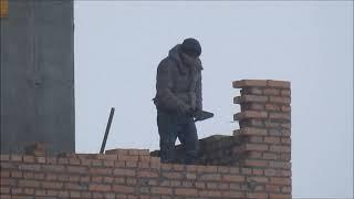 Каменщик на стройке Строительство высотки в Киеве