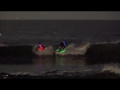 Surfers brave the night to avoid traffic on the waves