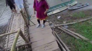 2years old baby walking bamboo bridge across mekong river at luang prabang