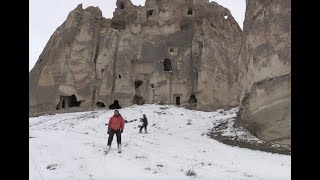 Nature-loving skiers enjoy skiing among fairy chimneys in the snow-covered valleys in Cappadocia