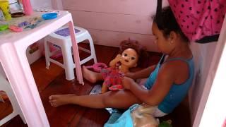 Nicolly arrumando a casinha de bonecas.