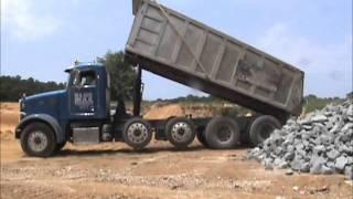 Blue Max Truckings Peterbuilt dump trucks delivering Rip Rap.