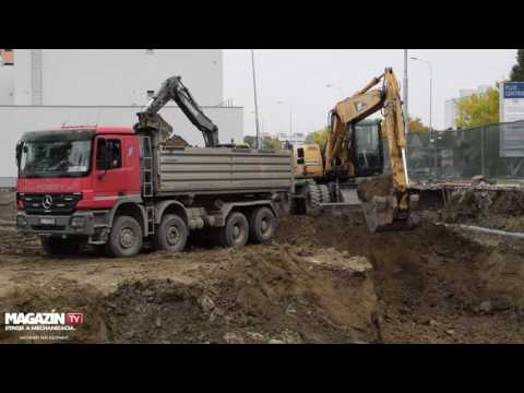 Wheel excavator CAT M318C digging and loading dirt to Mercedes-Benz ACTROS 4144 dump truck
