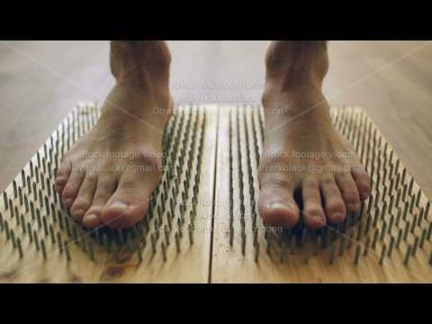 Closeup of yoga man stand on board with sharp nails
