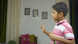Young cute boy enjoying and making soap bubbles in casual clothing - childhood fun