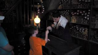 A wand chooses a boy inside Ollivanders Wand Shop in The Wizarding World of Harry Potter