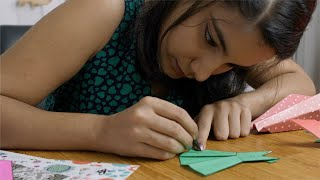 Young Indian girl decorating a piece of craft with a black sketch pen