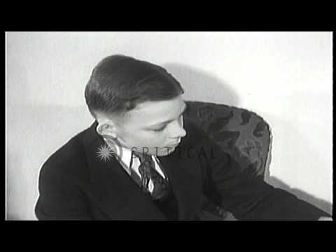 A young boy seated on a sofa listens to a radio in the United States. HD Stock Footage