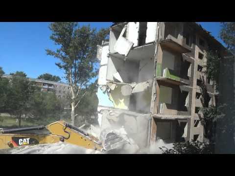 Снос пятиэтажного здания экскаватором.
