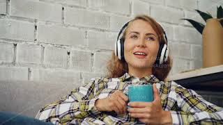 Relaxed girl student is listening to music wearing headphones, singing and holding cup of coffee