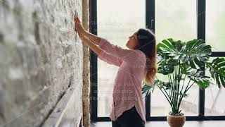 Creative woman is decorating her loft style apartment choosing place on brick wall for beautiful