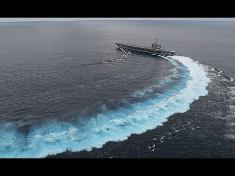 Gigantic aircraft carrier performs high speed turns