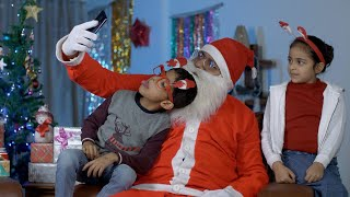 Funny Santa Claus taking selfies with young kids during Christmas celebration in India