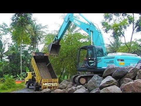 Dump Truck And Kobelco SK200 Excavator Unloading Stone