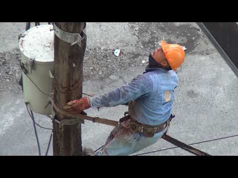 Electrical Power Lineman, Chain Saw, cuts Pole, Metro Manila