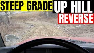 Dump truck backing up steep grade fresh material.