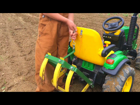 Farm Kid Driving Modified John Deere Toy Tractor With Cultivating Tines In The Garden