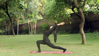 A young girl practicing veerbhadrasana / warrior yoga pose outside in a park