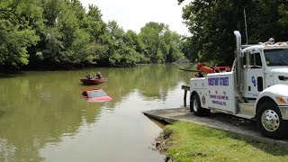 Police pull car out of river.