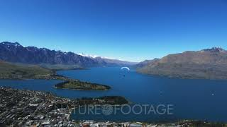 Download a paraglider takes off from skyline in queenstown, new zealand