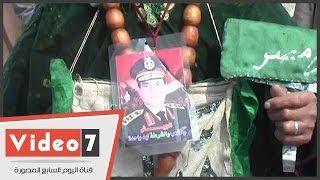 أحد مجاذيب الحسين يرتدى سلسة كبيرة عليها صورة المشير السيسى