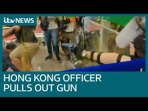 Hong Kong protests: Police officer pulls out firearm at airport | ITV News
