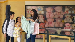 Indian girl showing her siblings her new top outside a toy store in a shopping mall