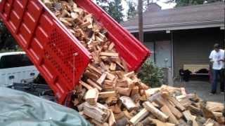 Dangerous dump truck unloading wood.