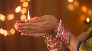 Beautiful hands of an Indian woman wearing bangles - holding a diya. Diwali Festival